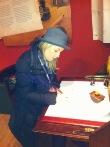 Fiona Sherlock writing at Jane Austen's writing desk