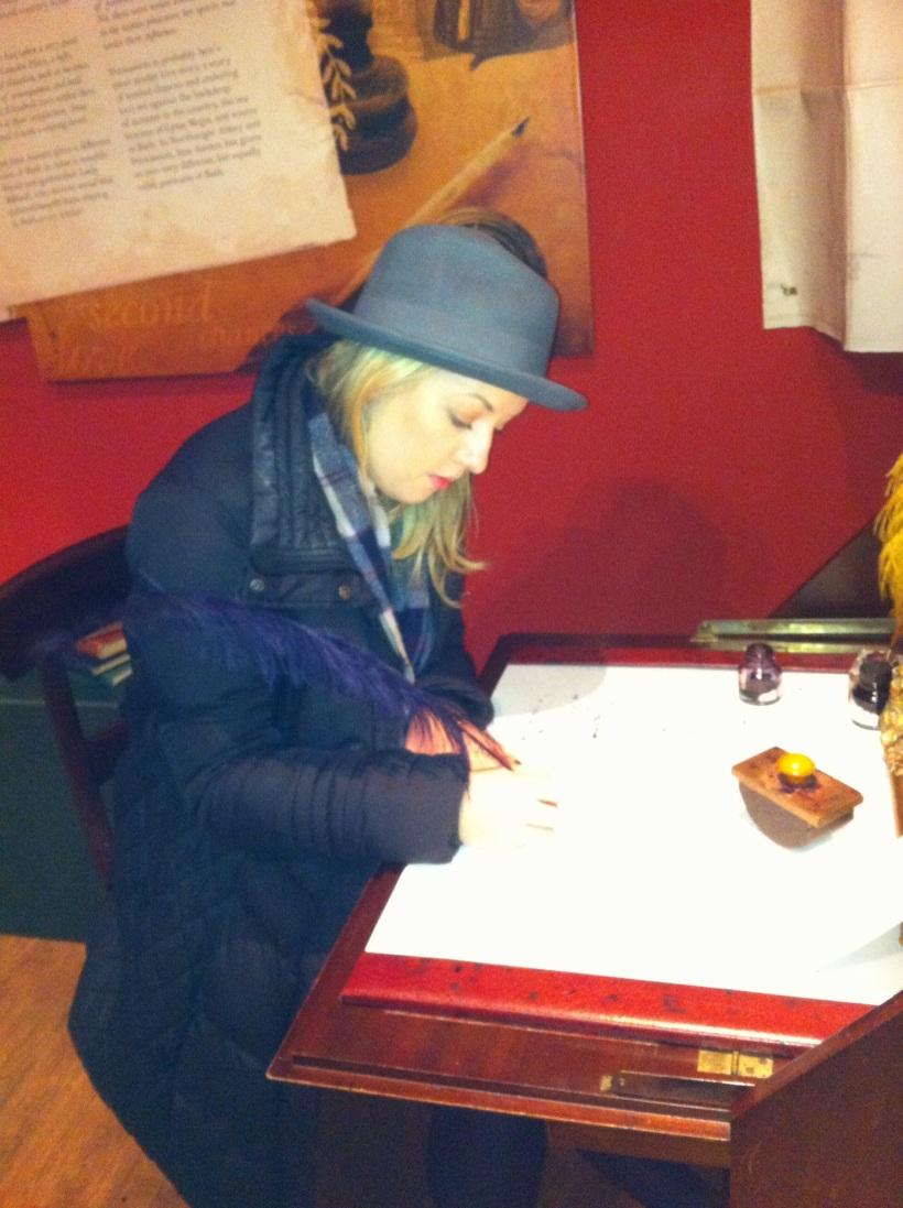 Fiona Sherlock writing at Jane Austen's writing desk