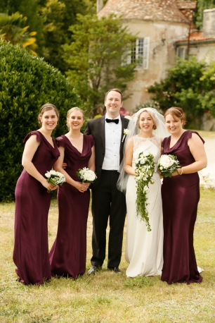 Bride, groom and bridesmaids at a wedding in France. Bridesmaids wearing burgundy Ghost dress. Groom wearing Louis Copeland. Bride wearing Thea from Folkster.